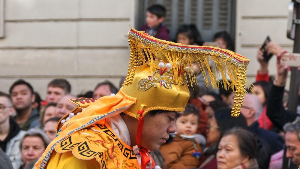 shallow focus photo of man wearing yellow headdress