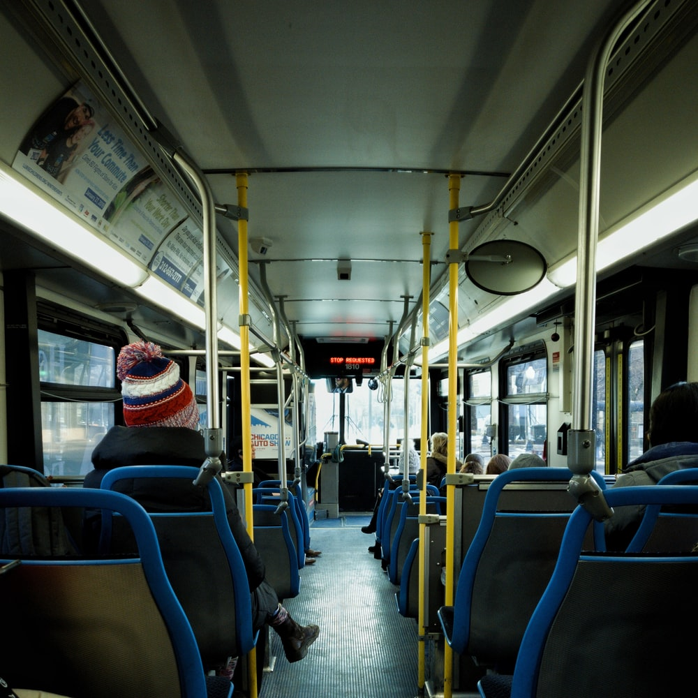 person in black jacket sitting on bus passenger chair
