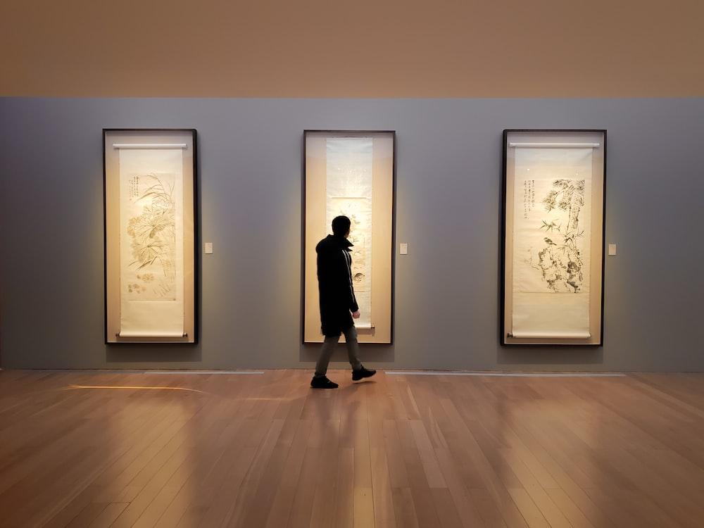 man in black jacket facing artworks