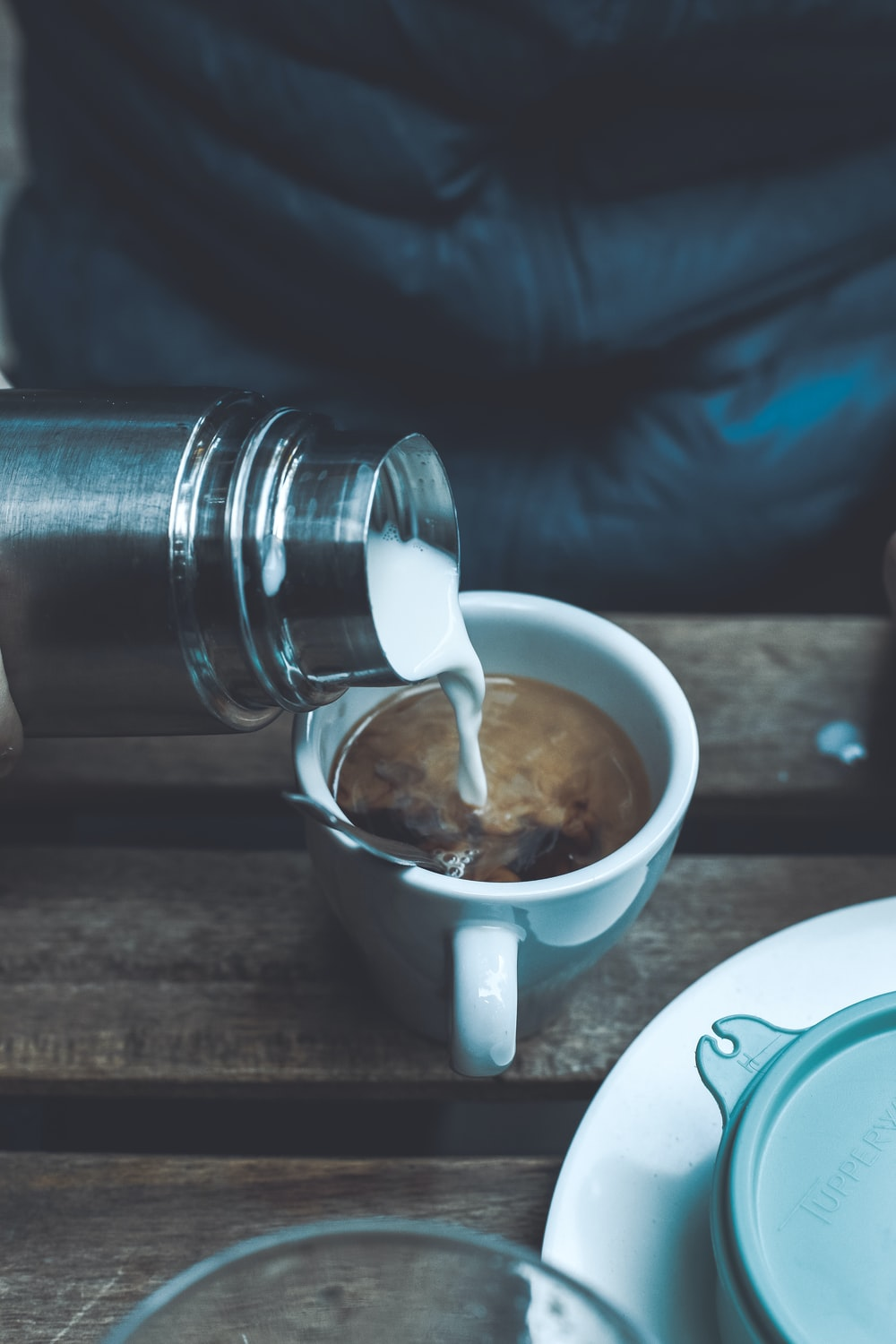 person pouring milk in coffee cup