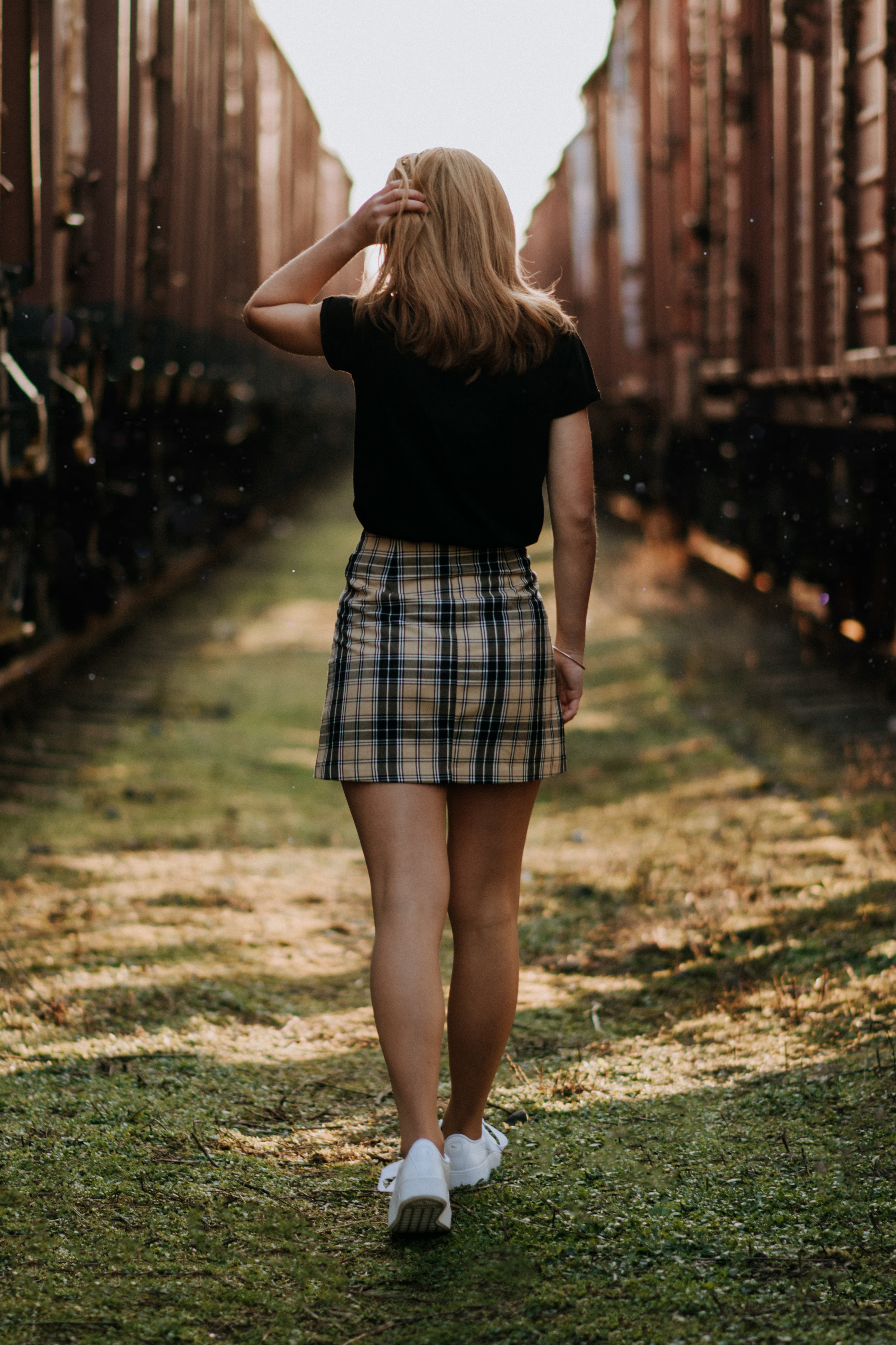 shallow focus photo of woman in white and black plaid mini skirt walking