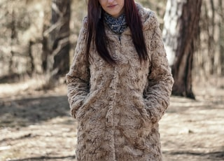 focus photography of woman wearing fur coat standing near trees during daytime