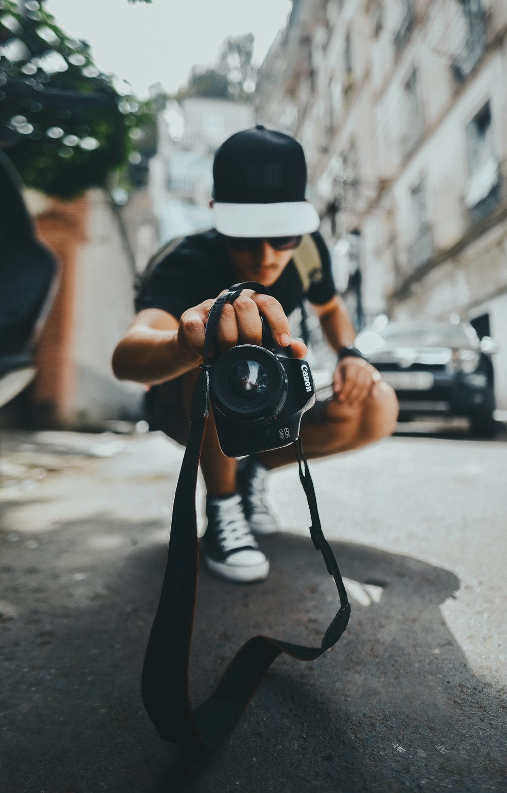 person wearing black and gray cap holding DSLR camera