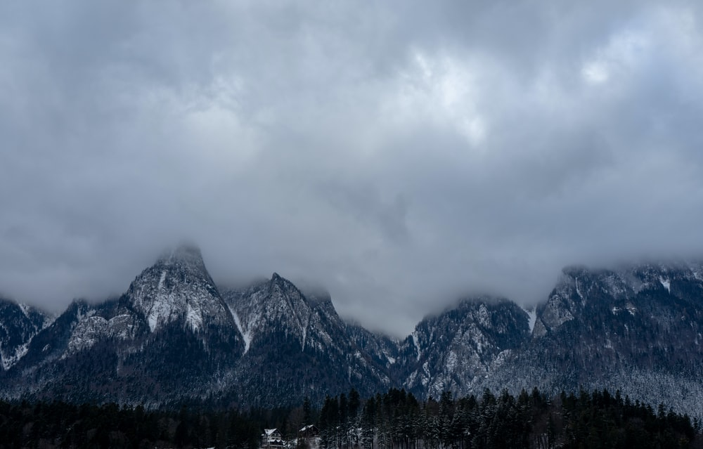 alps mountain under white clouds