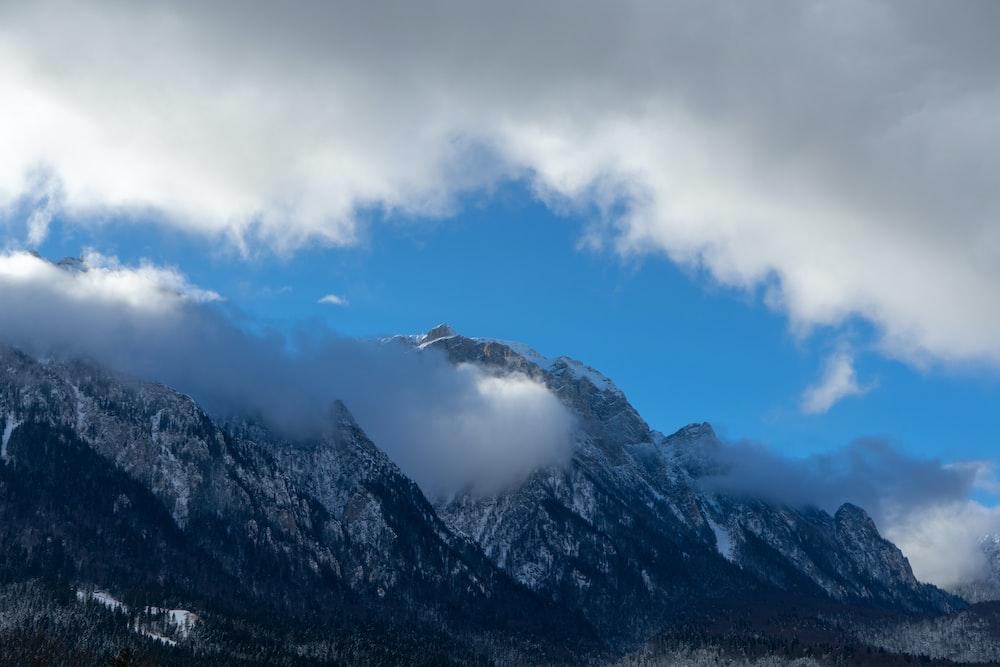 alps mountain under cumulus clouds