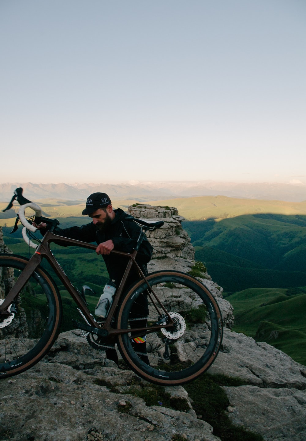 man carrying road bike at top of mountain