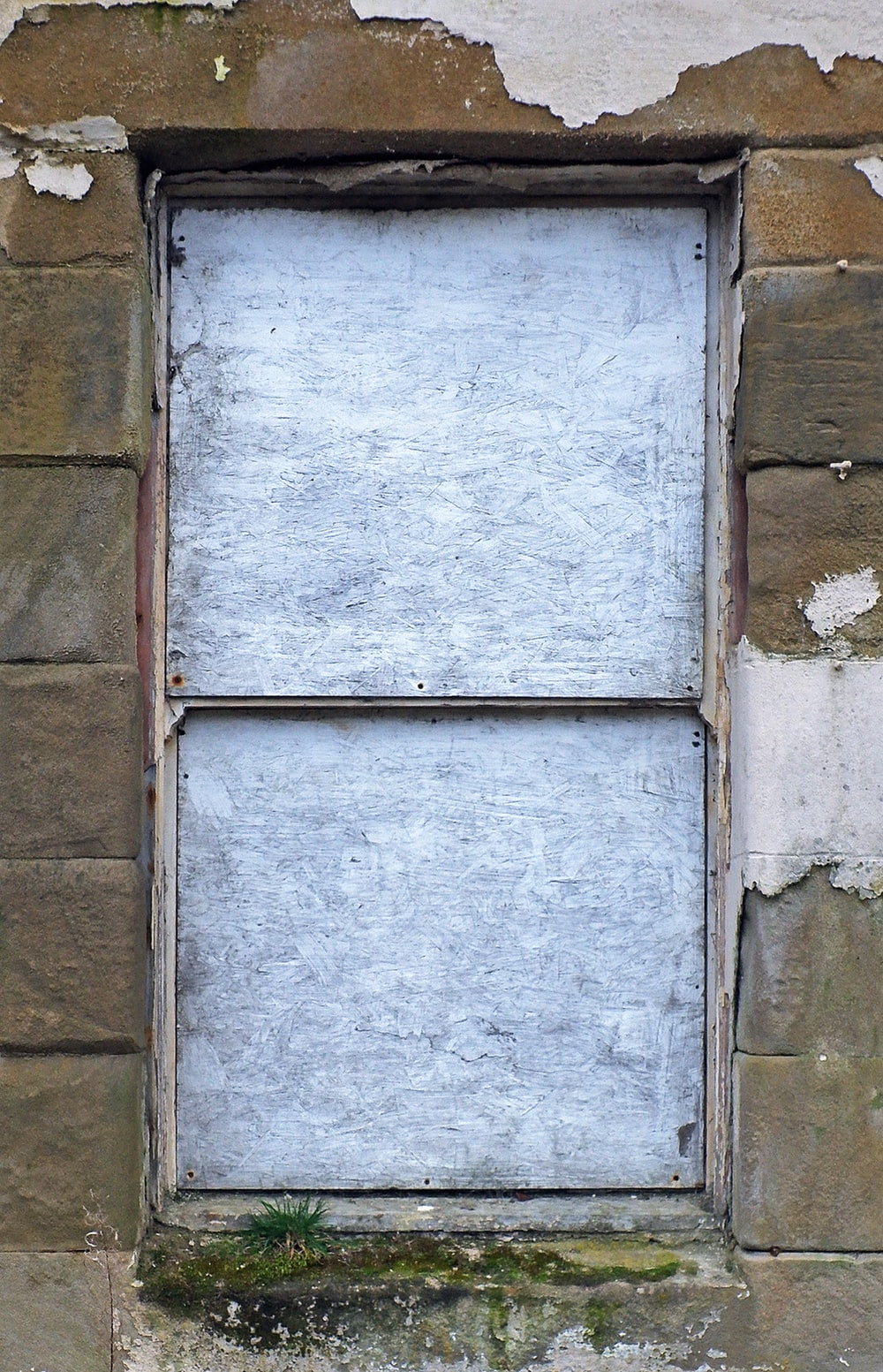 closed gray window on brown wall