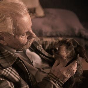 man in plaid jacket holding tan dog
