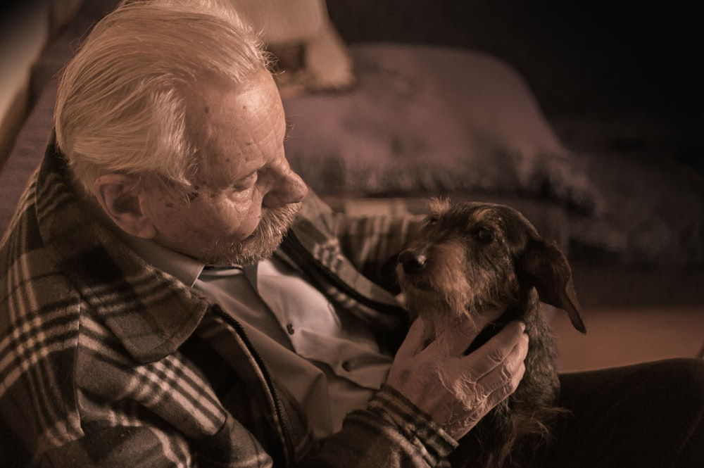 man in plaid jacket holding tan dog