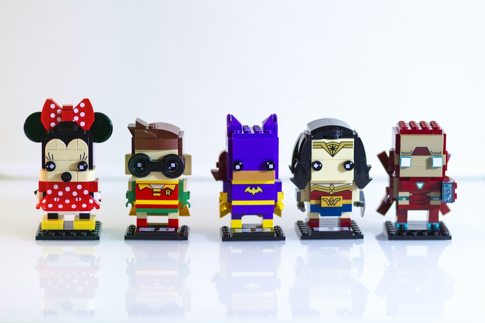 five assorted LEGO character figurines on white surface