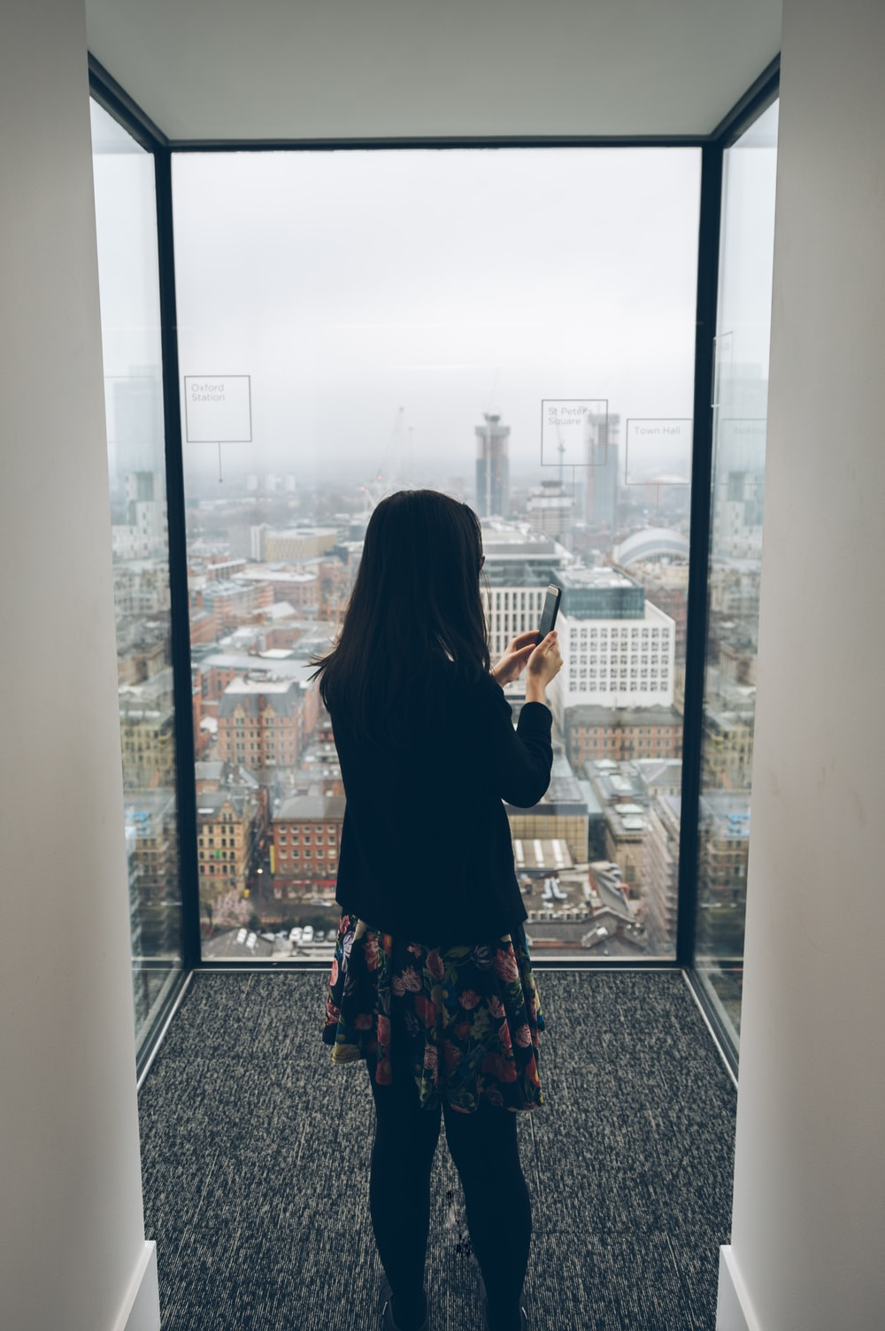 woman holding smartphone standing in front of window