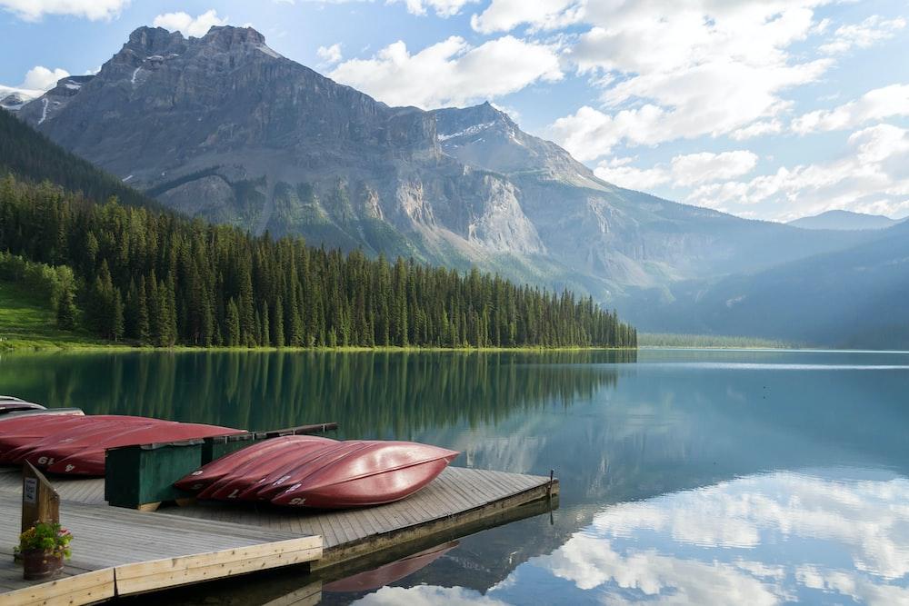 brown kayak on dock across mountains