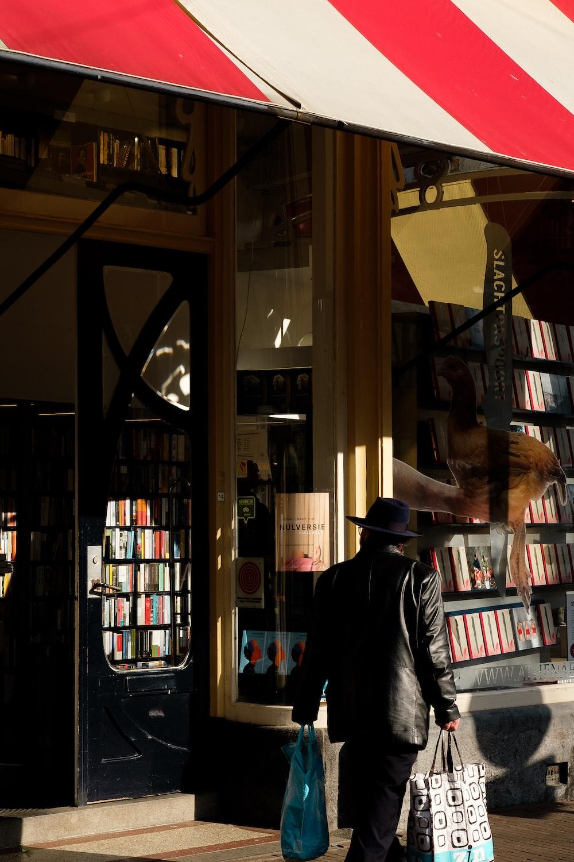man standing beside store facade