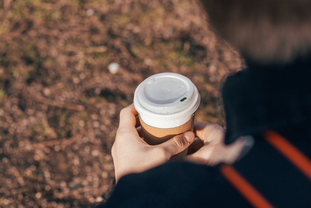 person holding white and brown cup