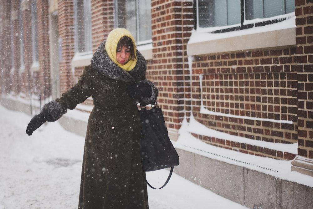 woman in black coat standing beside brick building
