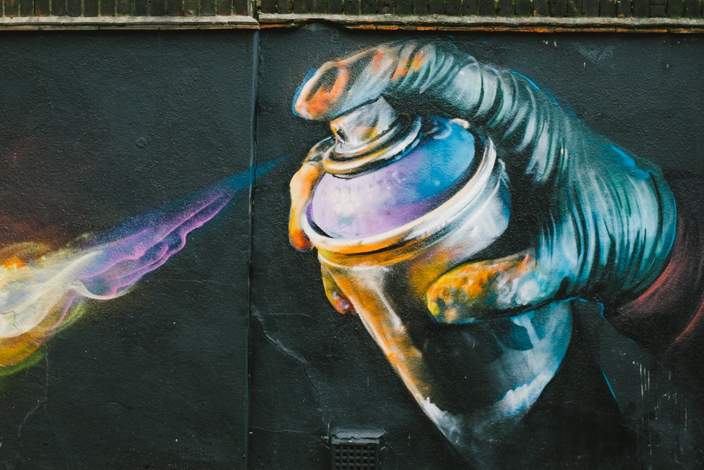person holding spray bottle painting