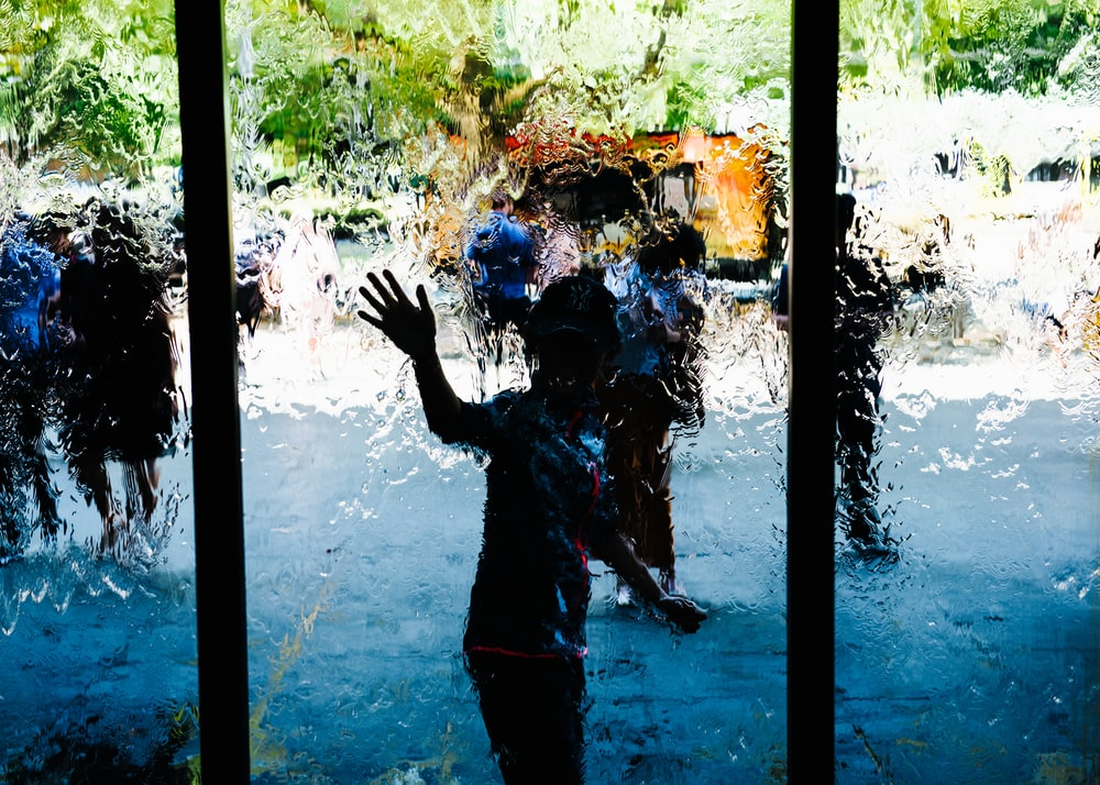 boy standing in front of glass panel