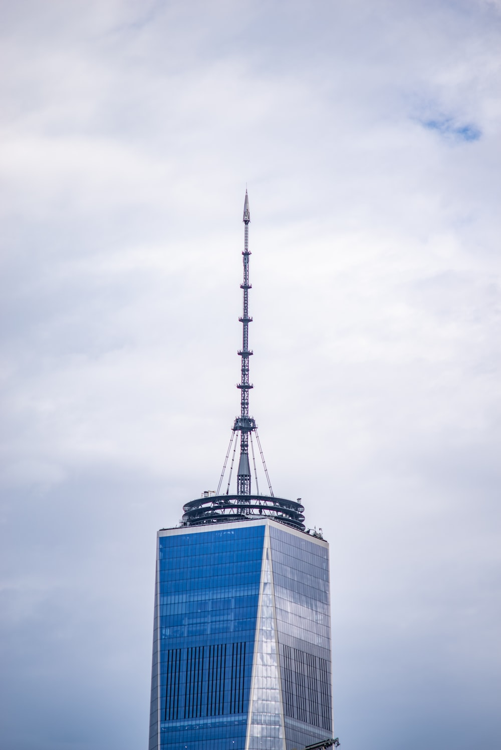 grey communication tower on top of blue and grey building