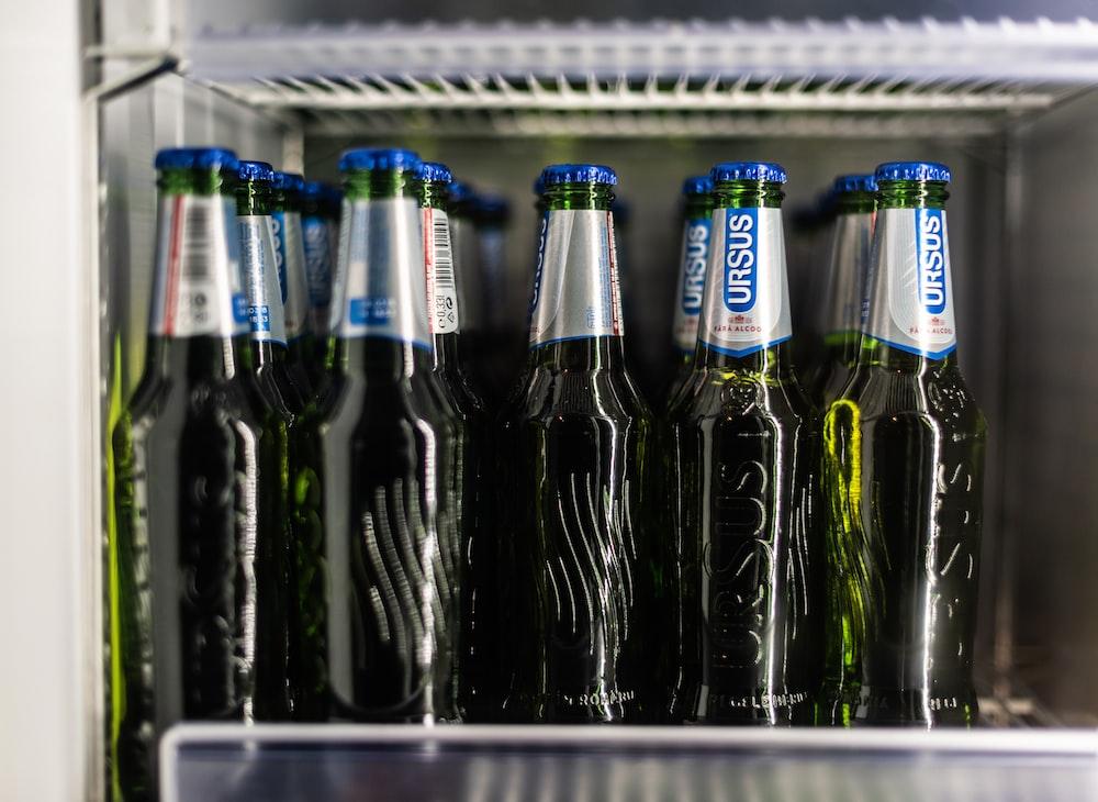 pile of Ursus beer bottles inside beverage cooler