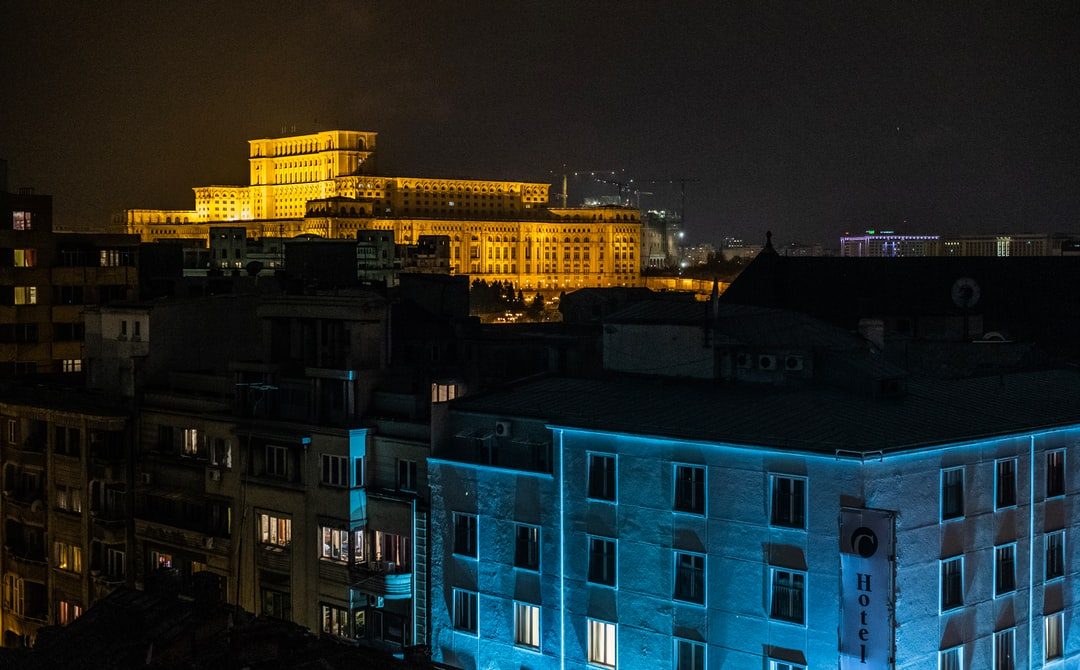 The yellow lit Romanian communist-era Palace of the Parliament - Ceausescu's most ambitious building project - in the background (a.k.a. House of the People) against a blue lit foreground building