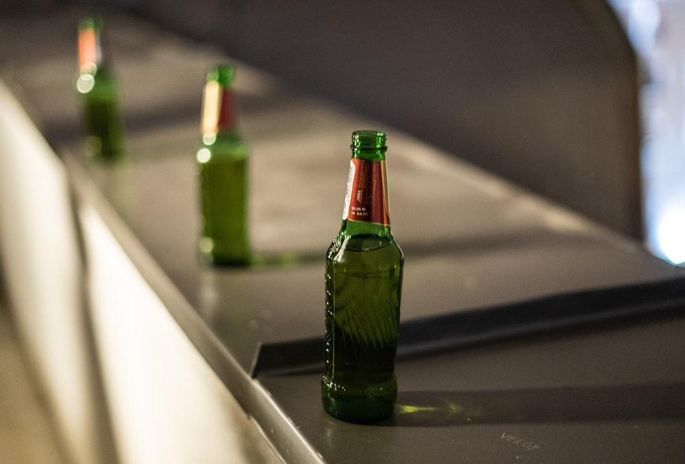 green glass bottle on table