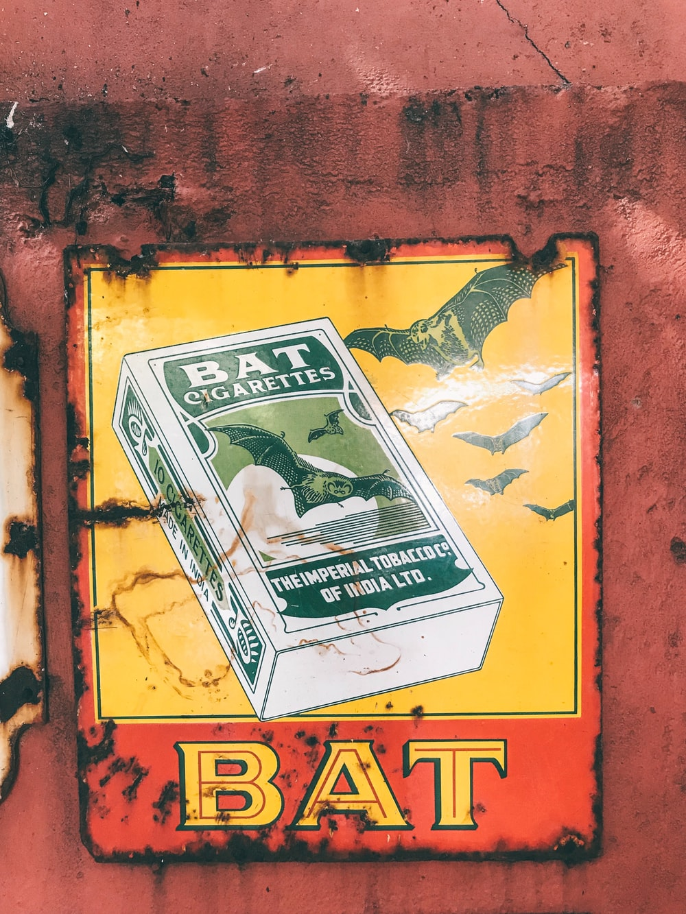 Bat Cigarettes poster on red wall
