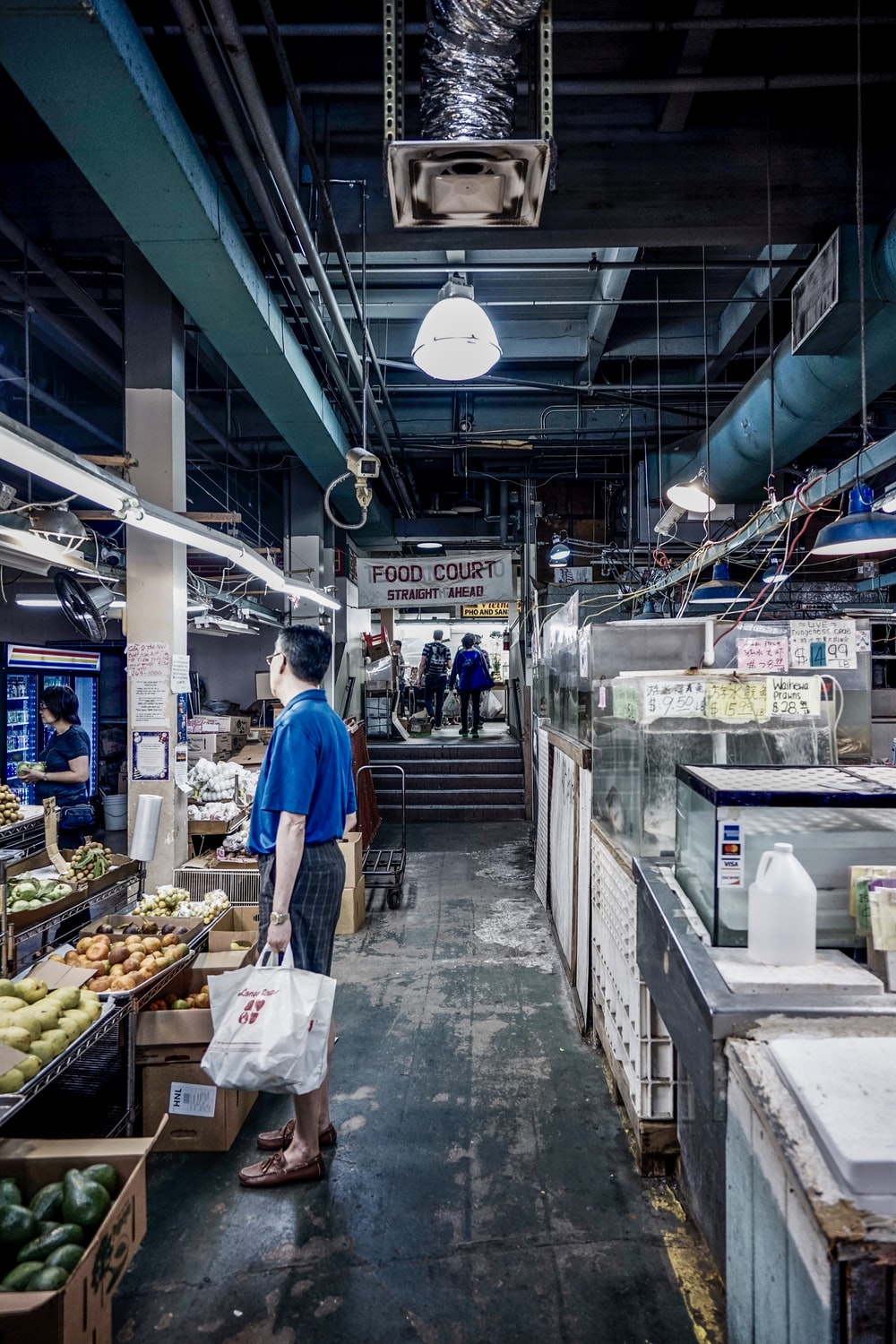 man holding shopping bag in food court