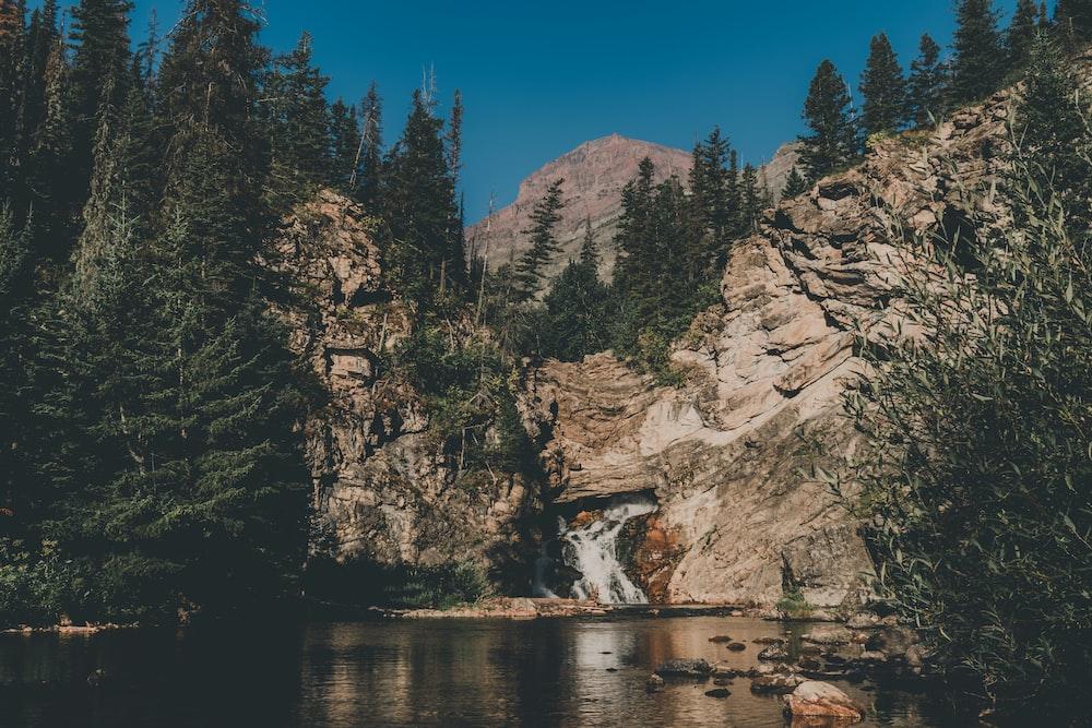 waterfalls in between rock boulders with trees