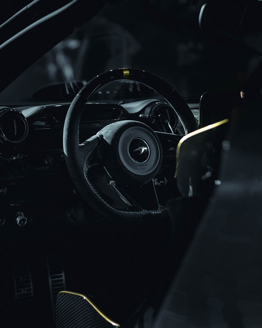 close-up photography of black vehicle steering wheel during nighttime