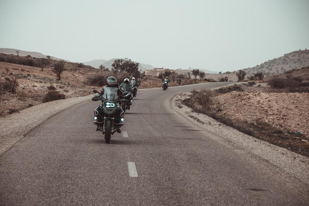 riders riding motorbike on asphalt road