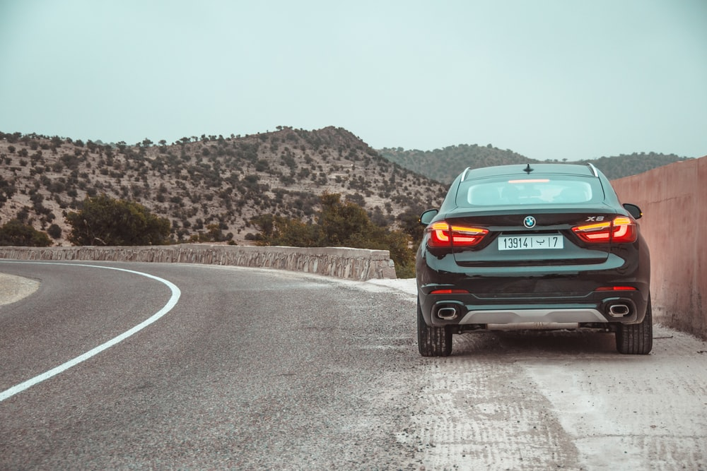 black BMW X6 parked on roadside with taillights turned on