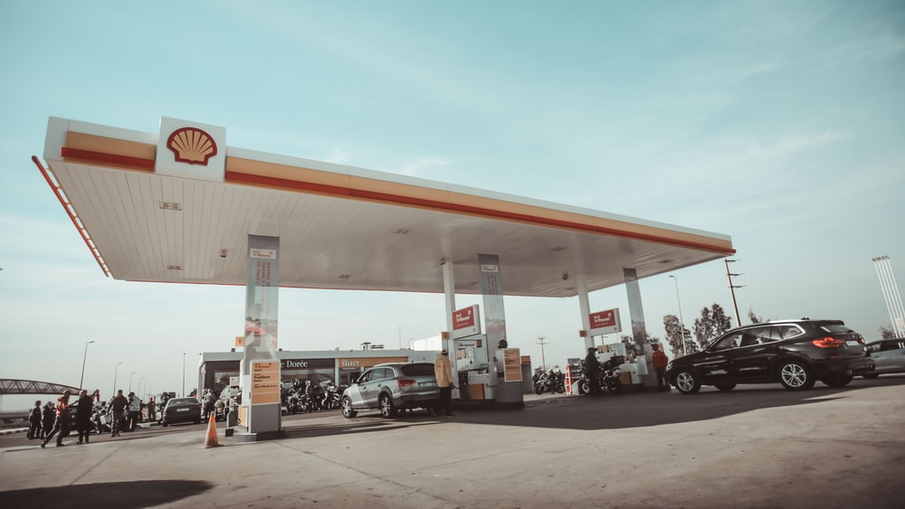 vehicles and people on Shell gasoline station during daytime