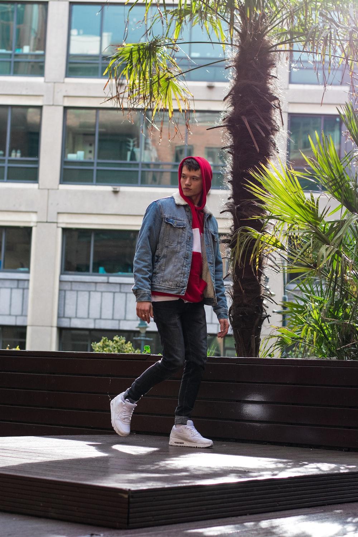 man wearing blue denim jacket standing beside palm trees