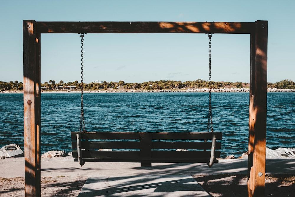 empty swing bench near body of water