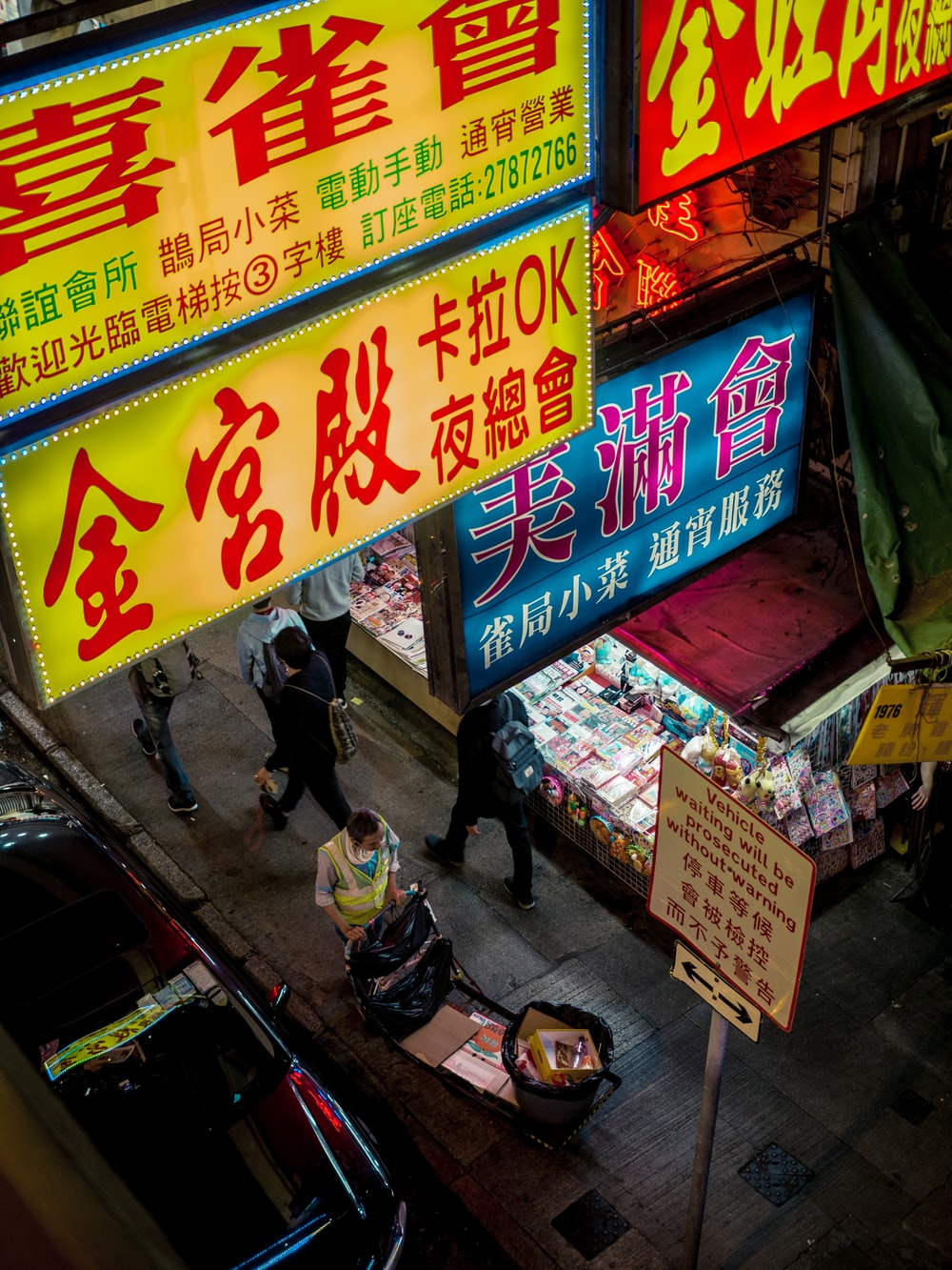 people walking on sidewalk under lighted store signs