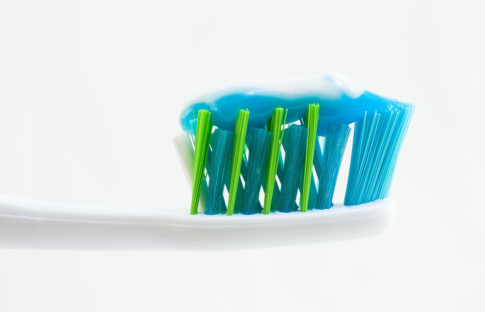 white, blue, and green toothbrush with blue toothpaste