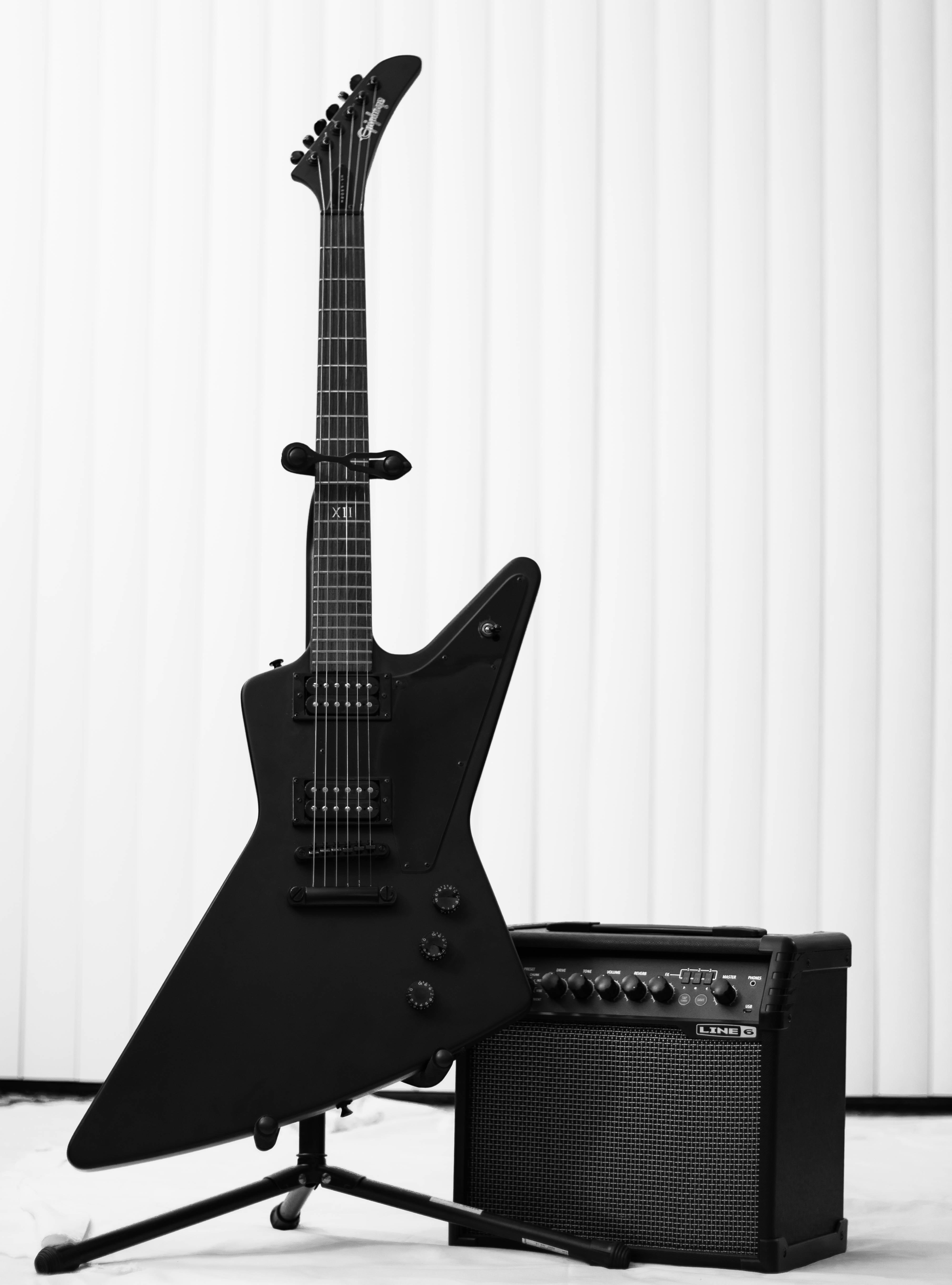 black electric guitar and amplifier