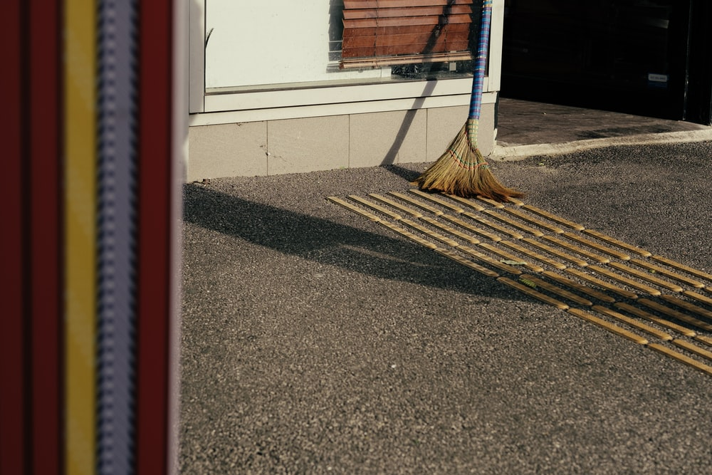 brown broom on gray concrete pavemebt
