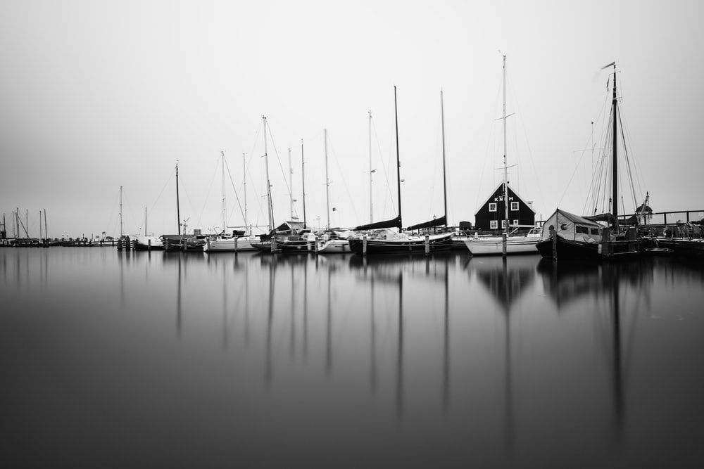 boats on body of water grayscale photo
