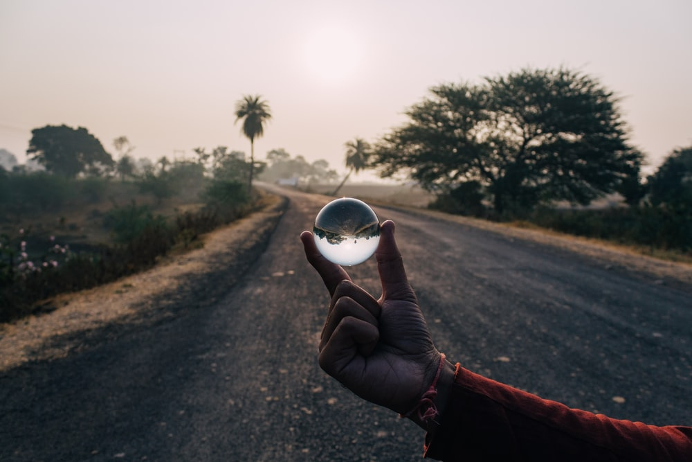 person holding clear ball decor