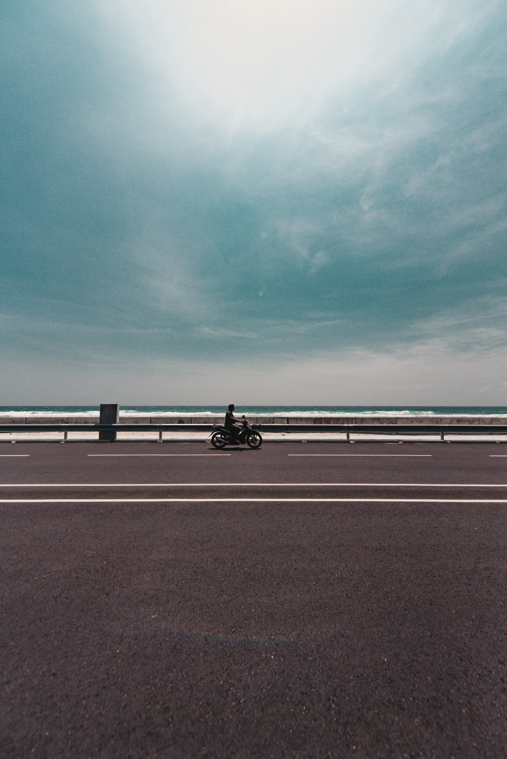 person riding motorcycle on empty road during daytime