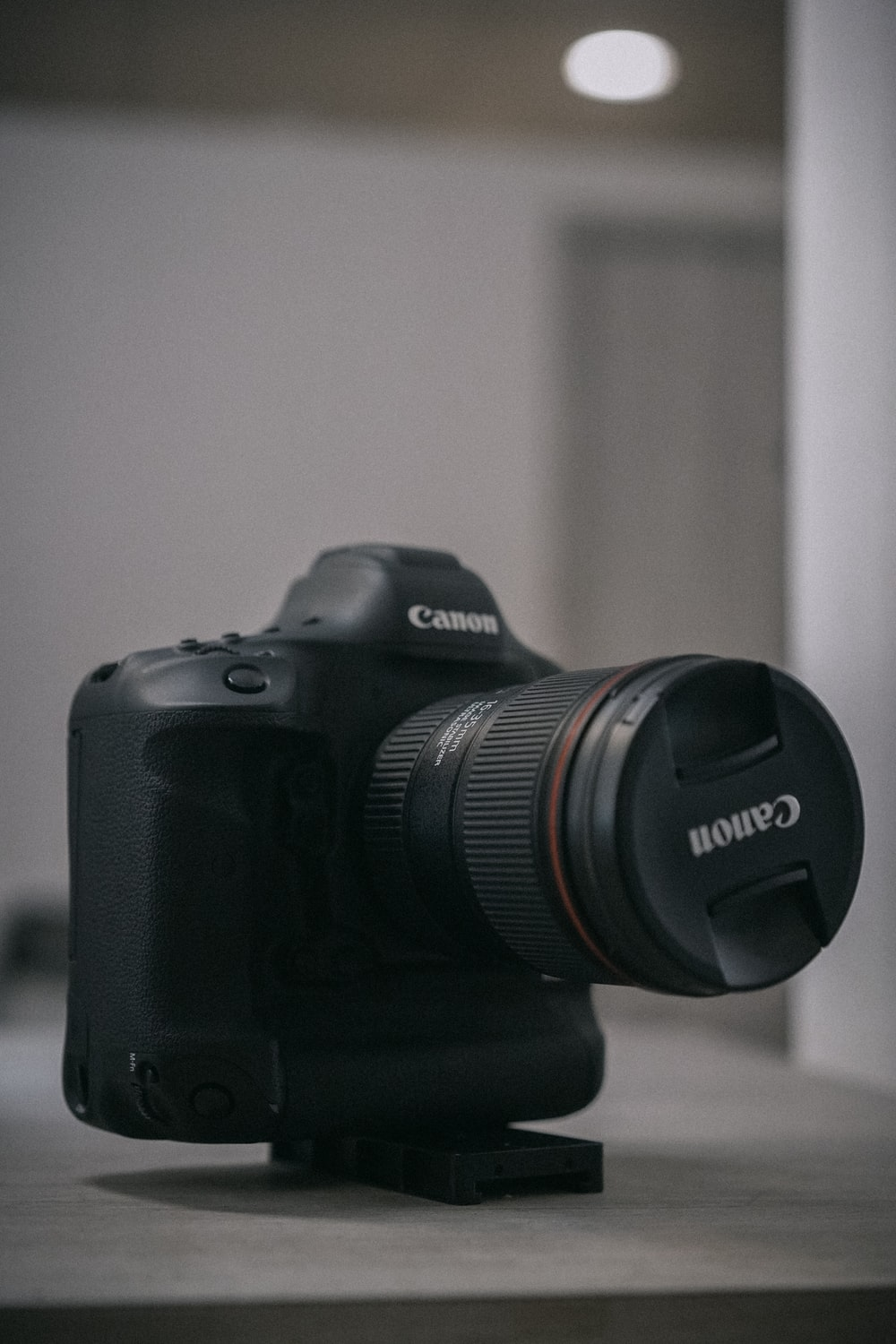 black Canon DSLR camera on brown surface