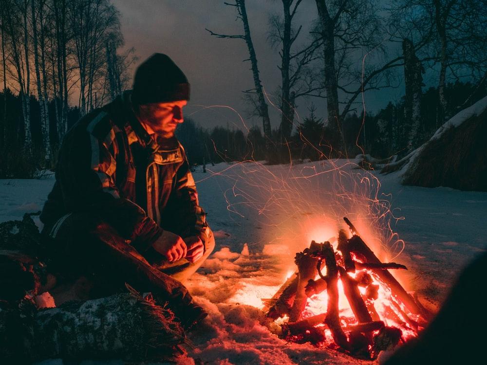 man sitting beside fire
