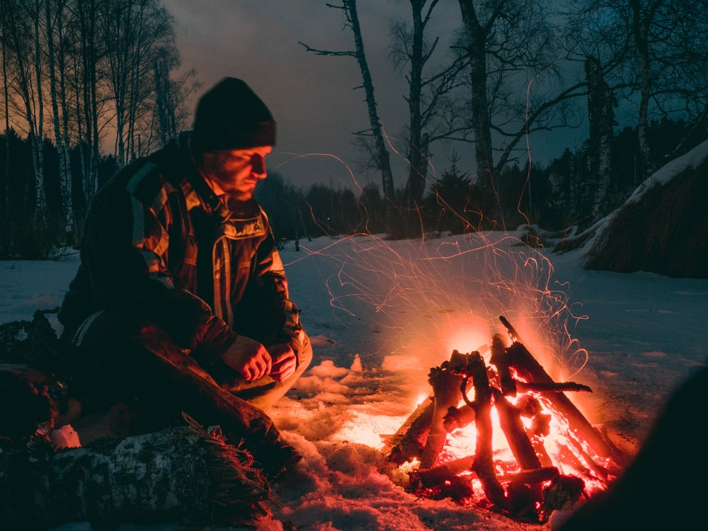 man sitting beside fire