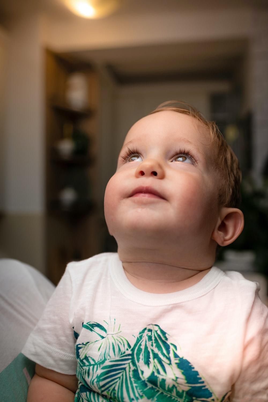 baby wearing white crew-neck shirt near white surface
