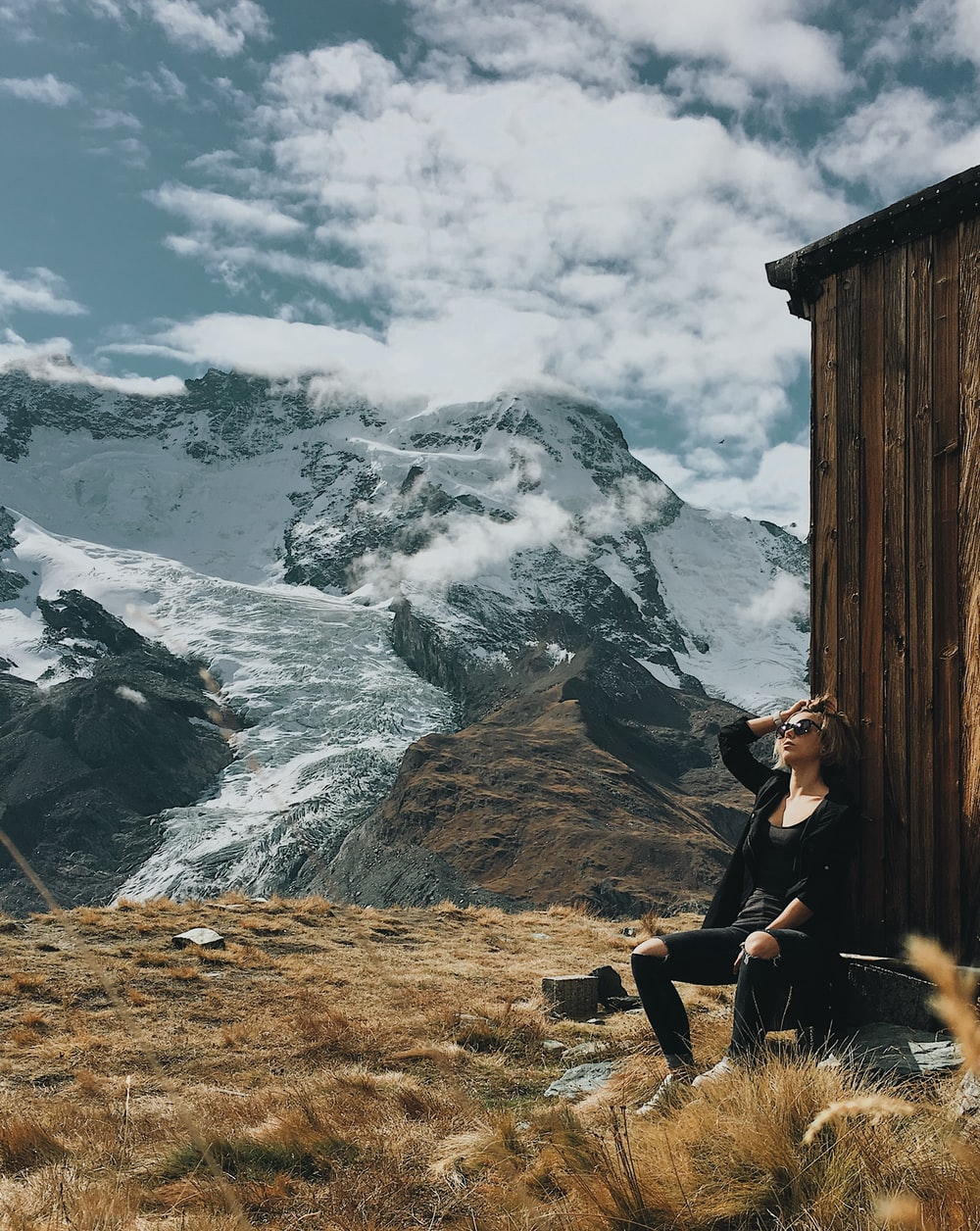 woman wearing black shirt sitting on rock with view of snow capped mountain