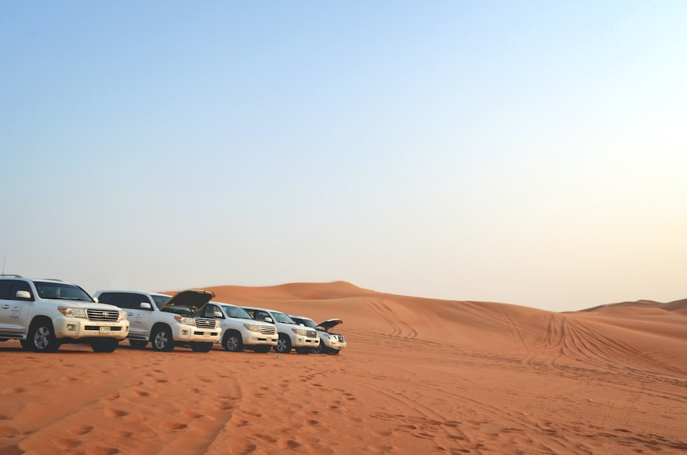 five white vehicles parked on desert