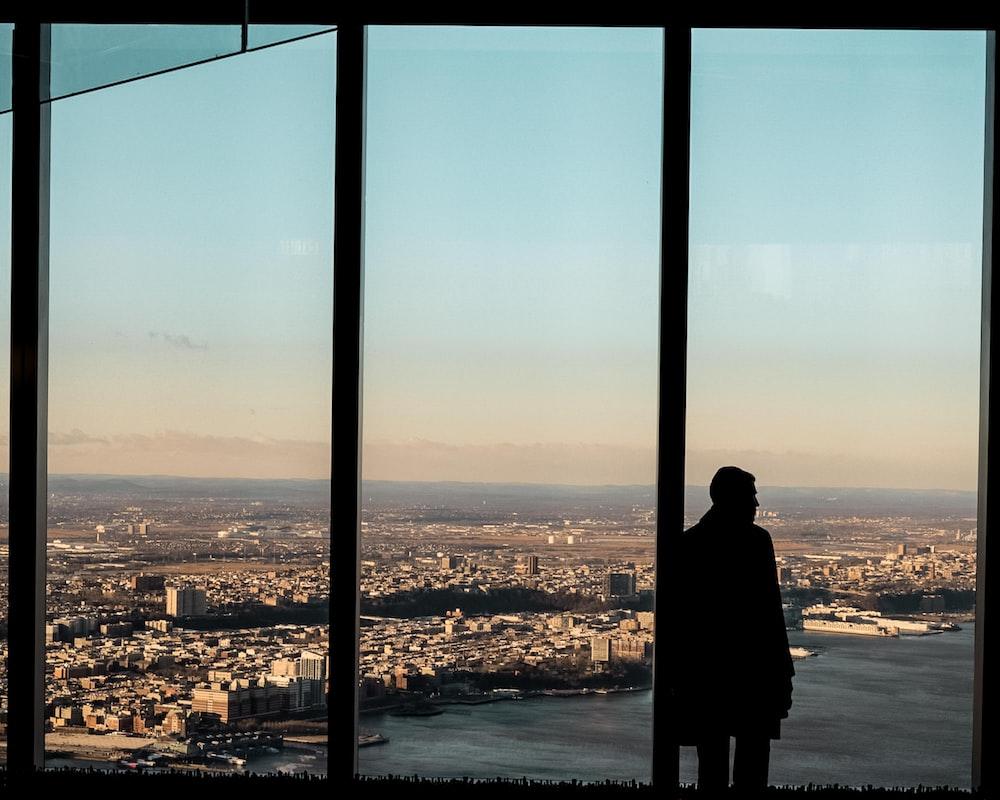 man standing beside glass wall