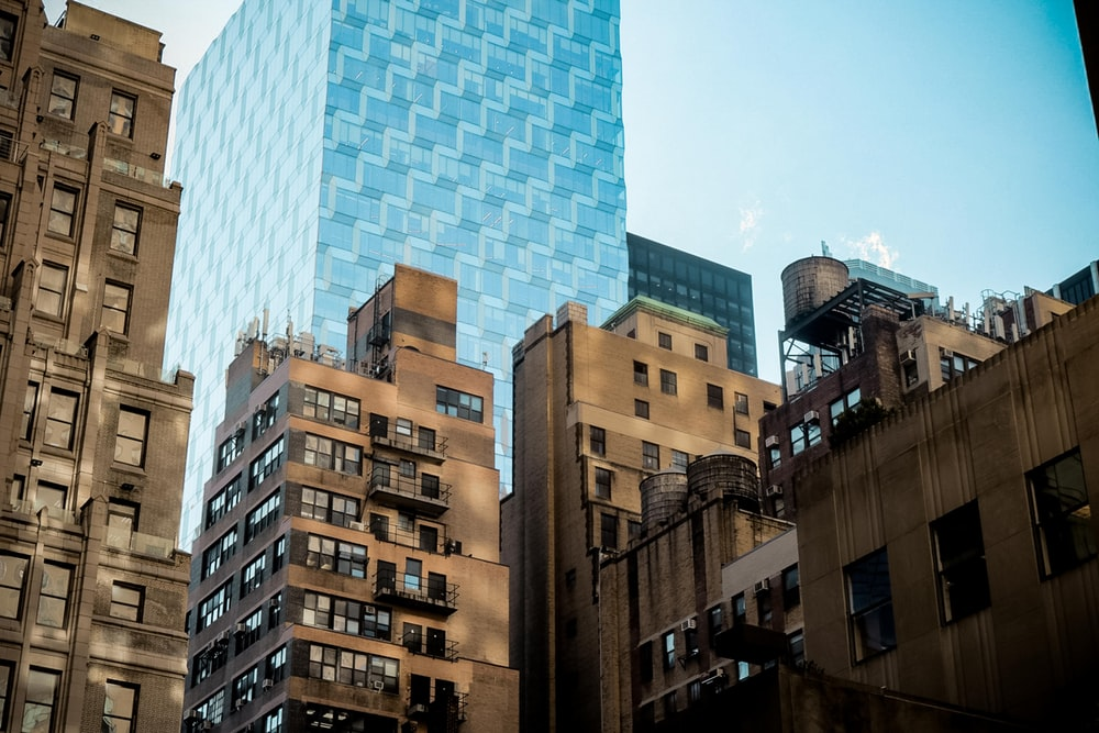 brown concrete building across blue tall building