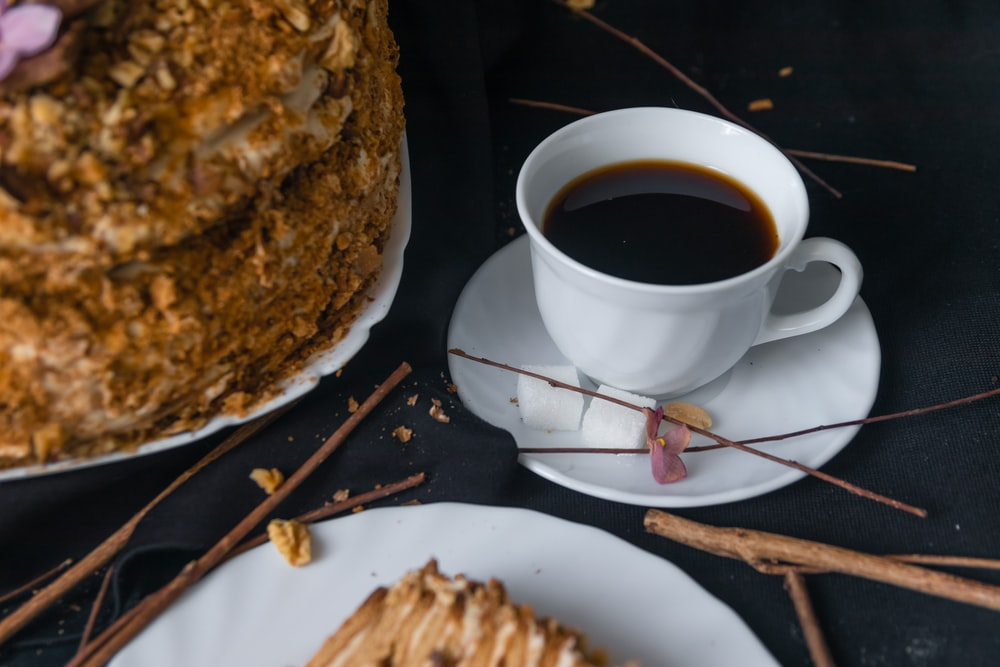 cup of black coffee on saucer beside cake